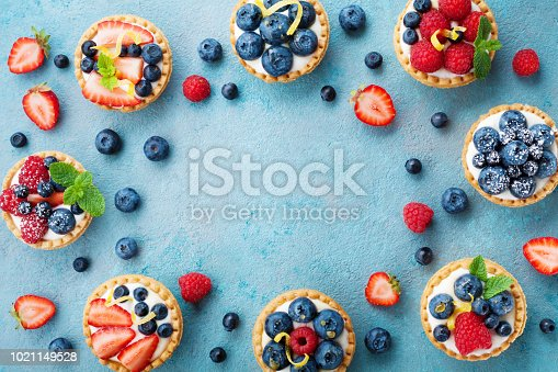 Tasty berry tartlets or cake with cream cheese and different berries around. Pastry dessert top view. Copy space for text.