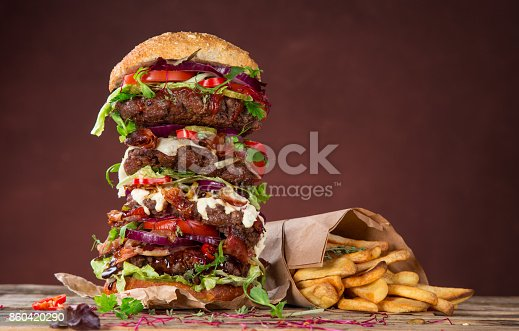 istock Tasty big burger on wooden table 860420290