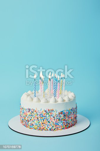 istock Tasty birthday cake with lighting candles on blue background 1070159778