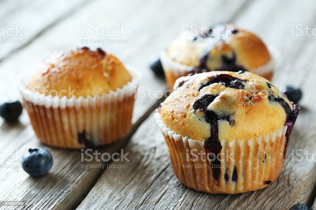 Tasty blueberry muffins on a grey wooden background stock photo
