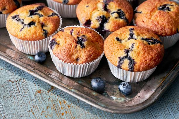 leckere blaubeer-muffins auf alten backblech auf rustikalen holz, text-raum sitzen - vanille muffins stock-fotos und bilder