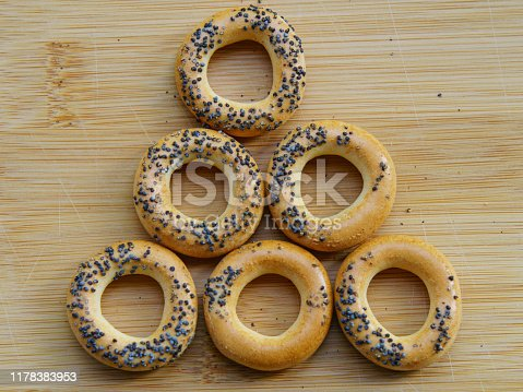 Photography of fresh delicious bread rings (bagels, sushki or baranki) with poppy seeds on the wooden background.