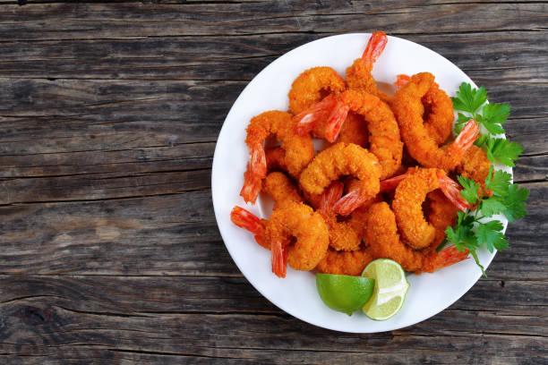 tasty breaded shrimps on white plate - жареный стоковые фото и изображения