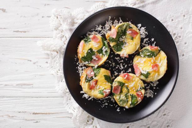 leckeres frühstück: frittata mit spinat, schinken und käse nahaufnahme. horizontale ansicht von oben - käsemuffins stock-fotos und bilder