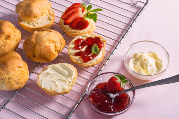 Tasty breakfast of scones with clotted cream and strawberry jam on pink background, top view stock photo