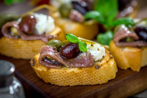 tasty bruschetta with anchovy, caper, olive oil ... - anchoa fotografías e imágenes de stock