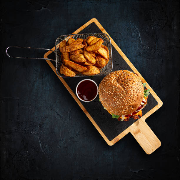 Tasty burger and golden potatoes stock photo