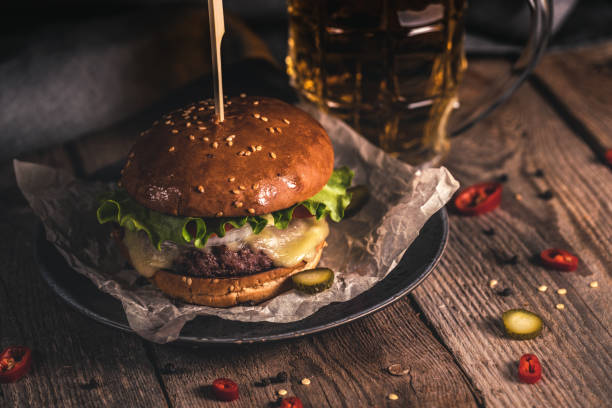 tasty burger and mug of beer on wooden table - burgers stock pictures, royalty-free photos & images