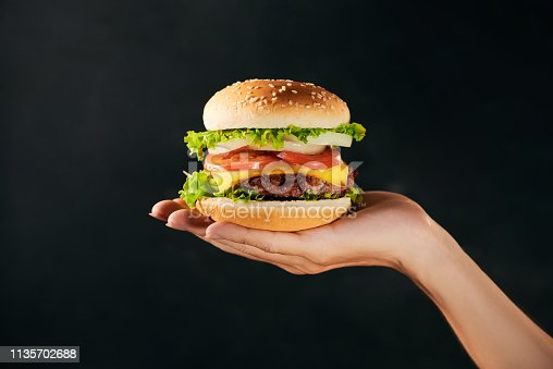 Tasty burger sandwich in hand isolated on black background