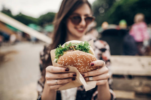 tasty burger. stylish hipster woman holding juicy hamburger in hands close up. boho girl with hamburger at street food festival. summertime. summer vacation picnic. space for text stock photo