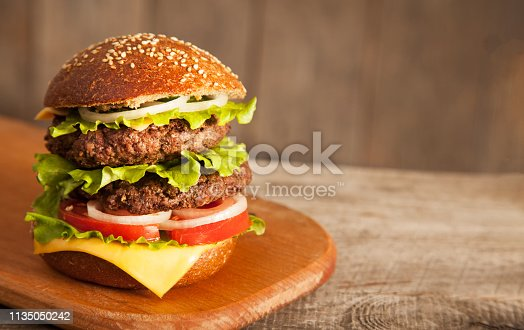 Tasty burger with cheese on wooden table.