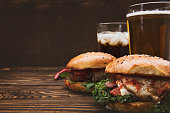 Fresh tasty burgers on wooden table with space on text