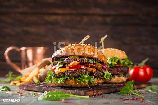 860251286istockphoto Tasty burgers on wooden table 859865342