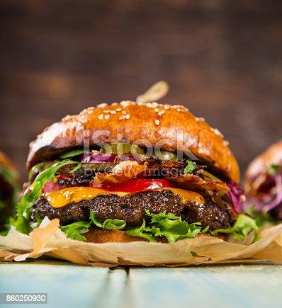 860251286istockphoto Tasty burgers on wooden table 860250930