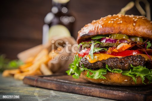 istock Tasty burgers on wooden table 860251286