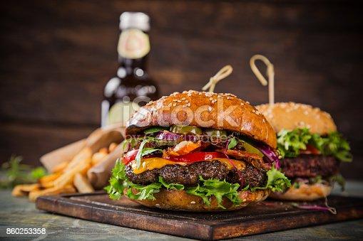 860251286istockphoto Tasty burgers on wooden table 860253358