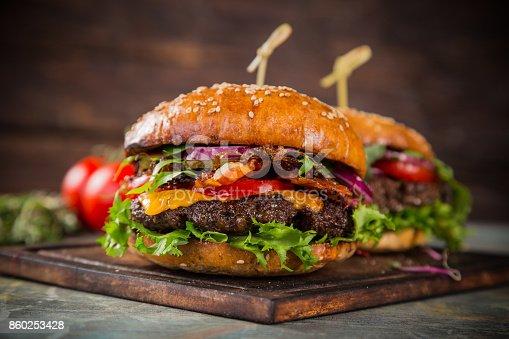 860251286istockphoto Tasty burgers on wooden table 860253428