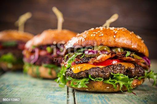 860251286istockphoto Tasty burgers on wooden table 860410962