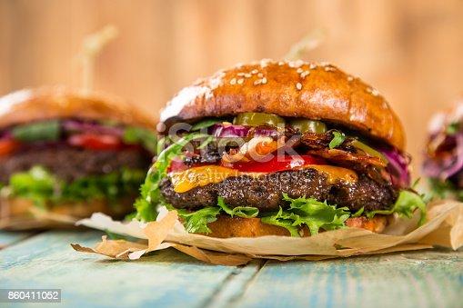 860251286istockphoto Tasty burgers on wooden table 860411052