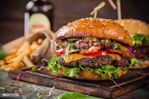 istock Tasty burgers on wooden table 860411132
