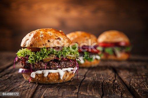 istock Tasty burgers on wooden table 944565172