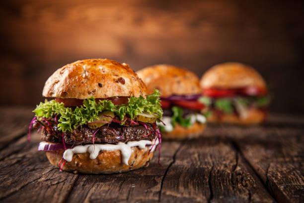 Tasty burgers on wooden table stock photo