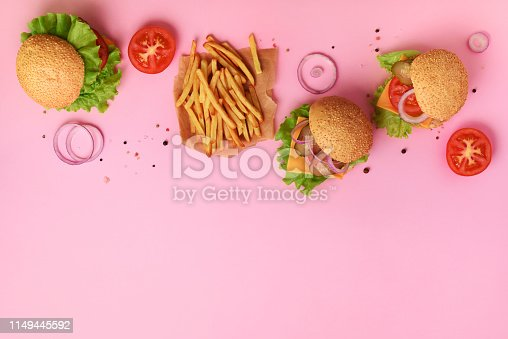 istock Tasty burgers with beef, tomato, cheese, onion, cucumber and lettuce on pink background. Top view, copy space. Fast food banner. Take away meal. Unhealthy diet concept 1149445592