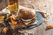Tasty cheeseburger, mug of beer and baked potato on a wooden table