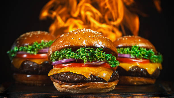Tasty cheeseburgers, lying on vintage wooden cutting board. stock photo