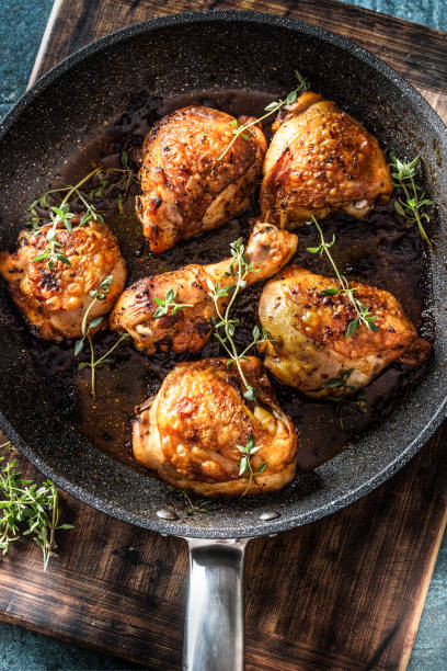 Tasty chicken legs roasted in ceramic pan with thyme - closeup stock photo