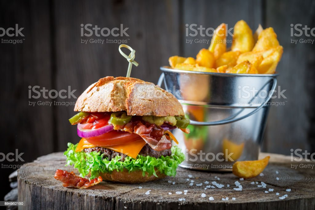 Tasty chips and hamburger made of beef, vegetables and cheese stock photo