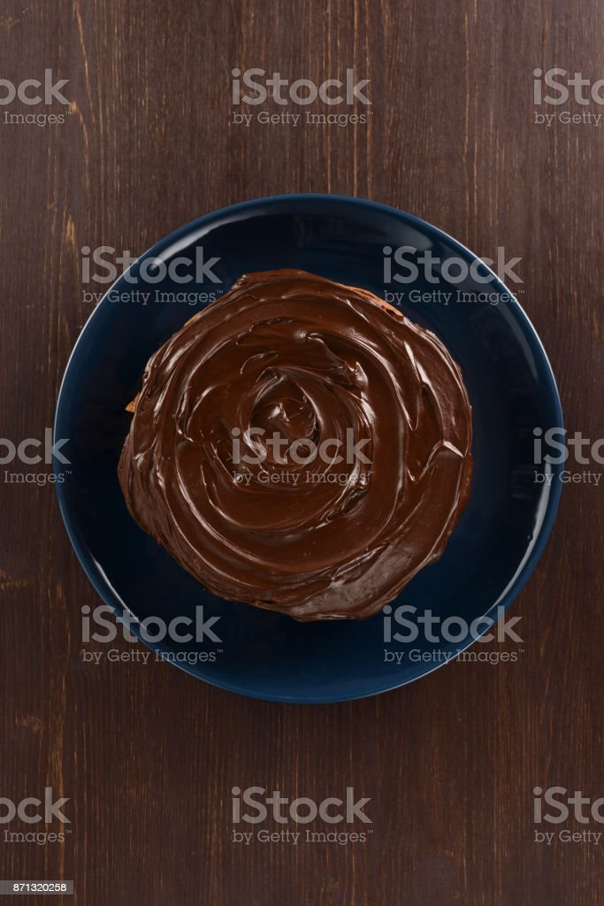 Tasty chocolate cake in dark blue plate on dark wooden table copy space stock photo