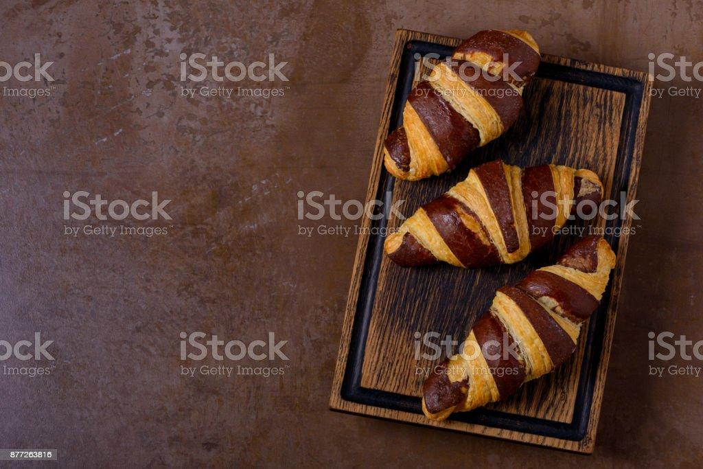 Tasty chocolate croissant on table stock photo