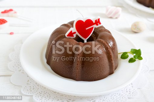 Tasty chocolate pudding on plates on a white wooden background. Light low-calorie dessert for breakfast.