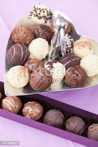 183269671 istock photo Tasty chocolate truffles on metal tray and in a box 471426227