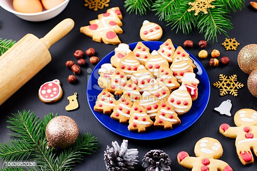 istock Tasty Christmas cookies, Christmas tree, decorations on black background. Christmas cooking concept 1063682036