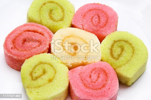 Tasty colorful bright muticolored roll cake on white plate background