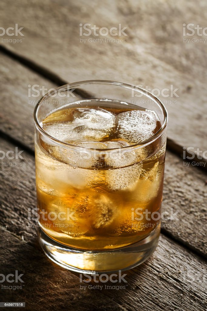 Tasty Colorful Cold Alcohol Drink Whiskey with Ice in Glass on Wooden Table. stock photo
