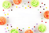 Tasty colorful cupcakes closeup on white wooden background