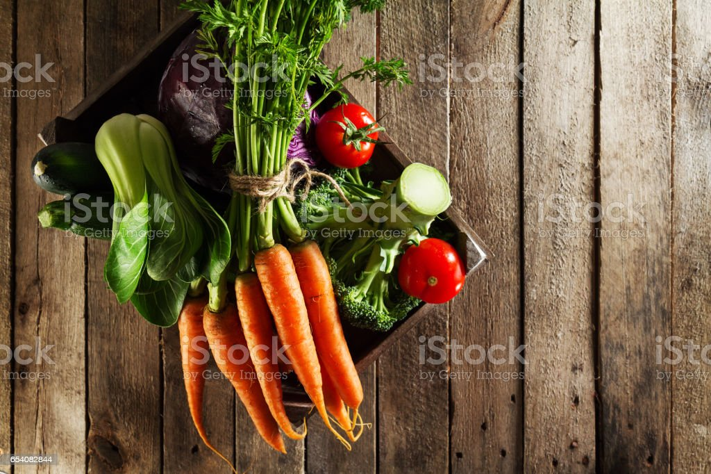 Tasty colorful fresh various seasonal vegetables in wooden box on wooden table. stock photo