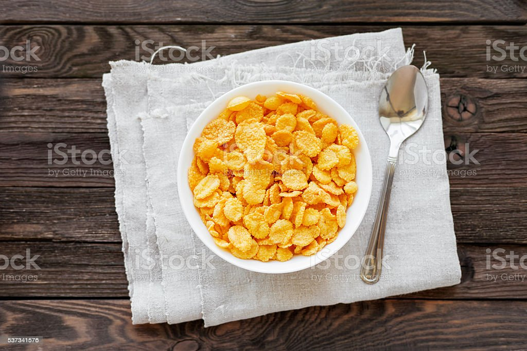 Tasty corn flakes in bowl. Rustic wooden background. stock photo