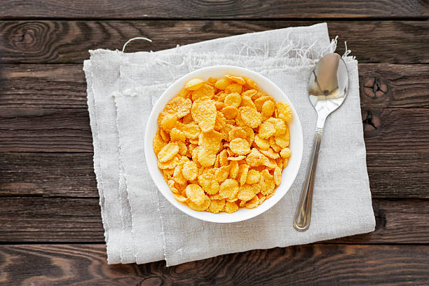 sabrosos copos de maíz (copos de maíz) en bowl. fondo de madera rústica. - corn flakes fotografías e imágenes de stock