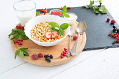 Tasty cornflakes with berries on wooden background Healthy tasty breakfast of muesli with strawberries, raspberries, black currants and red currants.