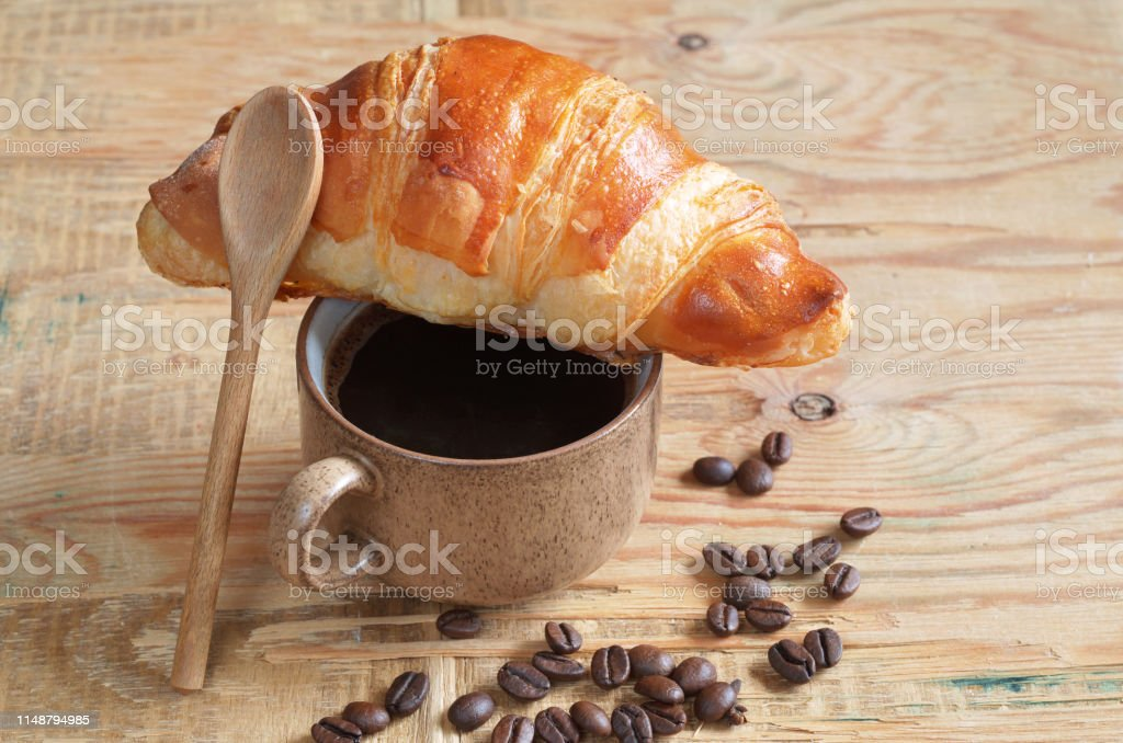 Tasty croissant and cup of coffee on the old wooden background close...