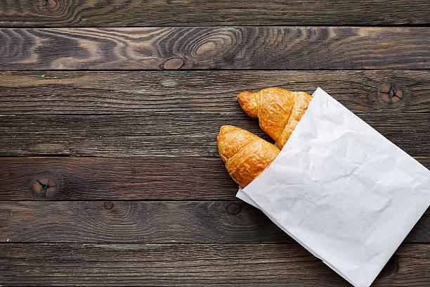 leckeren croissants im weißbuch tasche. rustikale hölzerner hintergrund. - brottorte stock-fotos und bilder