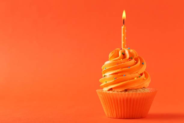 leckere cupcake mit kerze auf orangem hintergrund - cupcake, zuckerguss stock-fotos und bilder