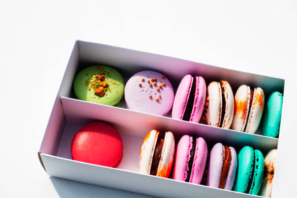 Tasty different colored macarons in white box on light background stock photo