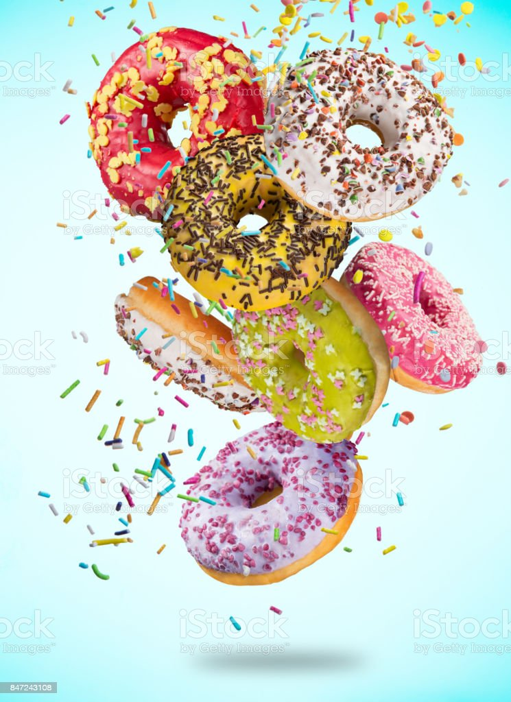 Tasty doughnuts in motion falling on pastel blue background stock photo