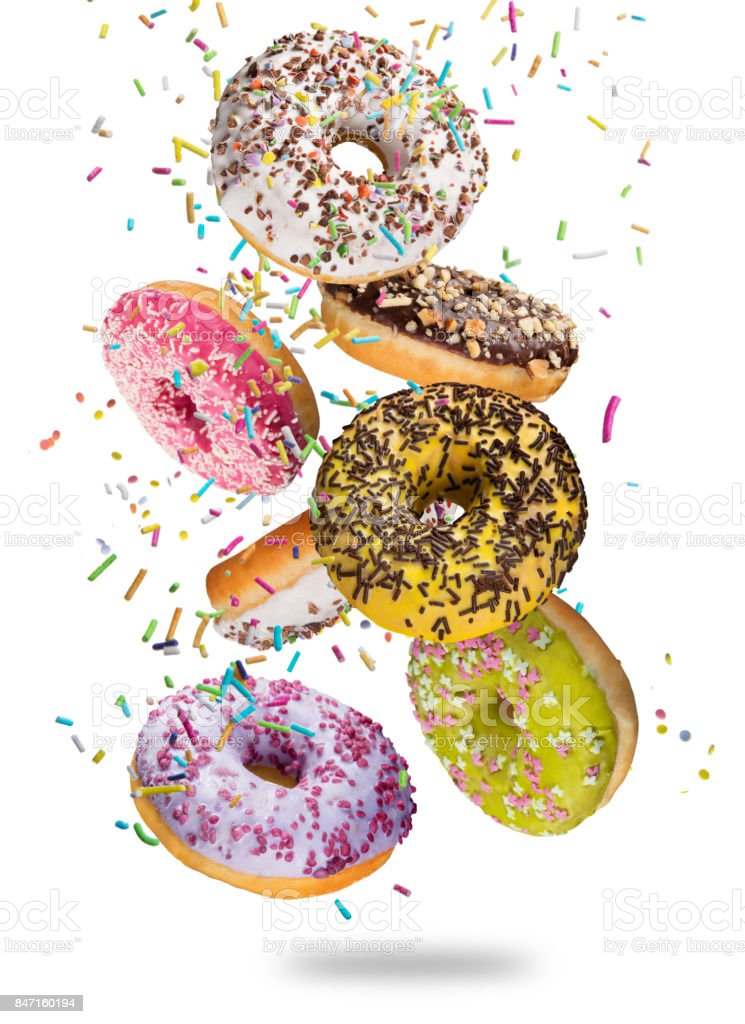 Tasty doughnuts in motion falling on white background stock photo