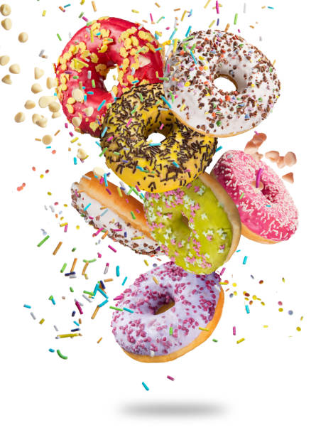 tasty doughnuts in motion falling on white background - stack rock stock pictures, royalty-free photos & images